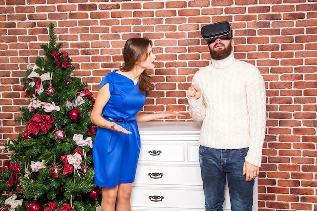Vr技術とカップル間の対立。 vrヘッドセットを使用している男性と彼の妻は新年に腹を立てています。