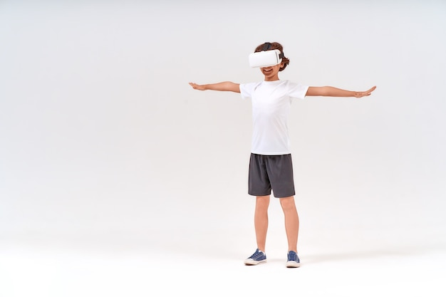 バーチャルリアリティまたはdメガネを身に着けているスポーツ服を着た10代の少年のvrテクノロジーフルレングスショット