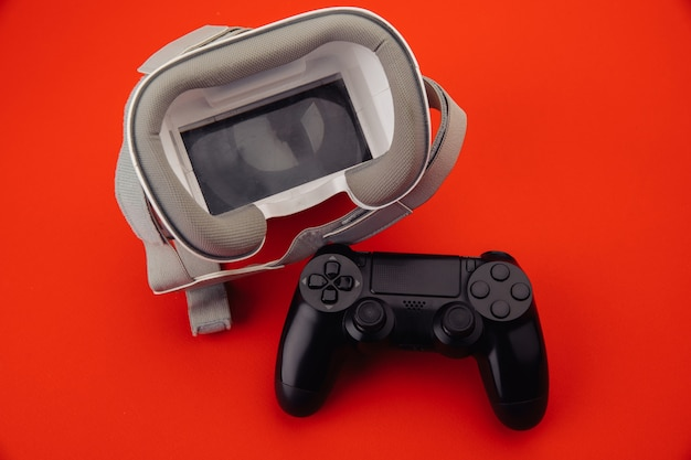 Vr virtual reality glasses with back gamepad on red background.
