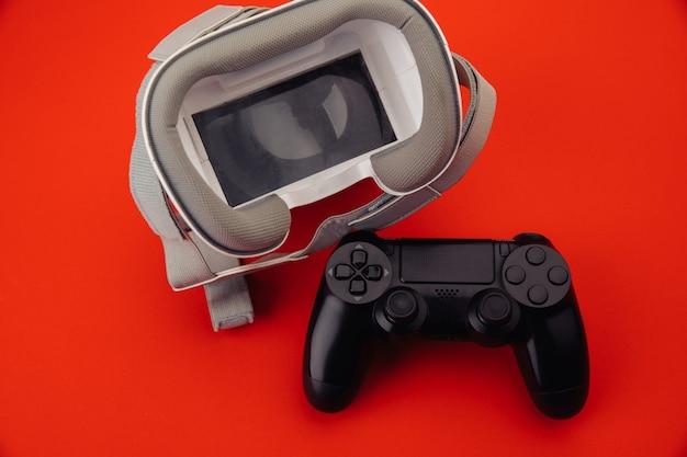 빨간색 배경에 게임 패드와 vr 가상 현실 안경.