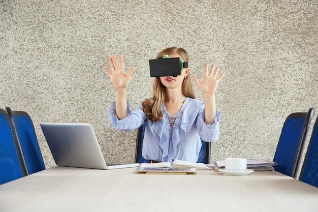 Vrヘッドセットを身に着けている女性がオフィスの机で身振りで示すショットを腰