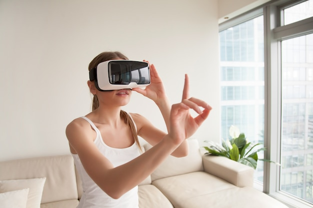 Женщина в гарнитуре vr касаясь виртуальных объектов