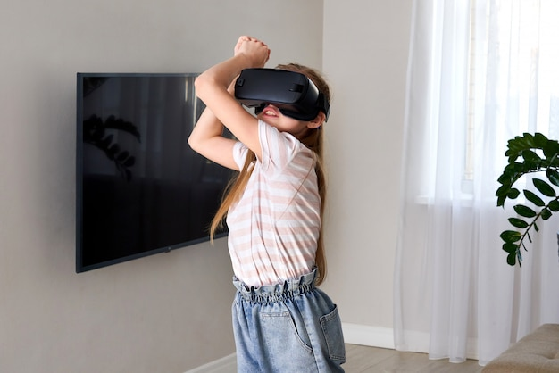 Девочка-подросток нося шлемофон изумлённых взглядов виртуальной реальности и играть, коробку vr. технология, новое поколение, концепция прогресса. девушка пытается коснуться объектов в виртуальной реальности.