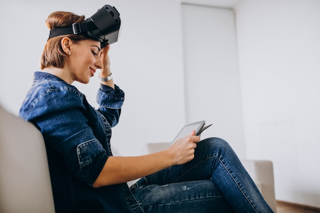 Молодая женщина в очках vr и с помощью планшета
