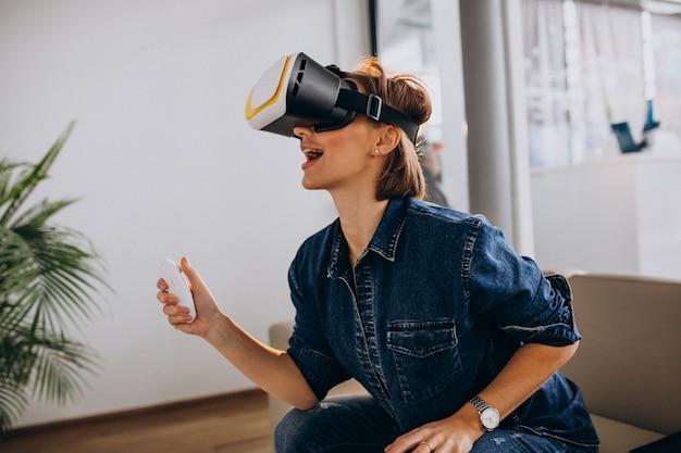 Молодая женщина в очках vr и играть в виртуальную игру, используя пульт