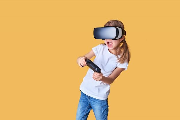 Девушка испытывает vr гарнитура против игры джойстик. удивленные эмоции на ее лице. ребенок с помощью игрового гаджета для виртуальной реальности.