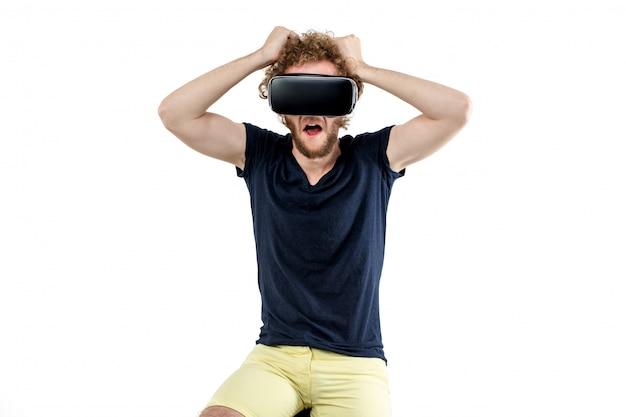Молодой кудрявый мужчина, используя гарнитуру vr и испытывает виртуозность