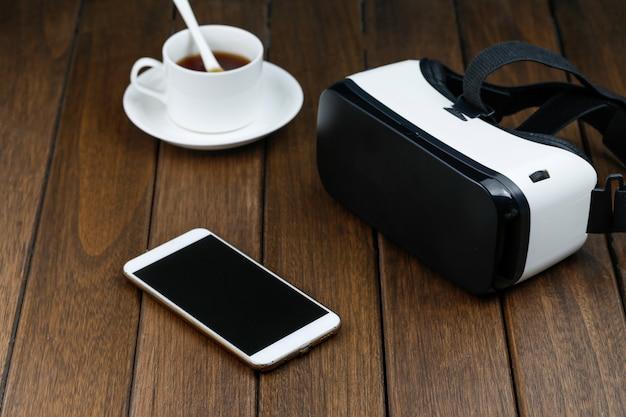 Vrの眼鏡と携帯電話の木製の机