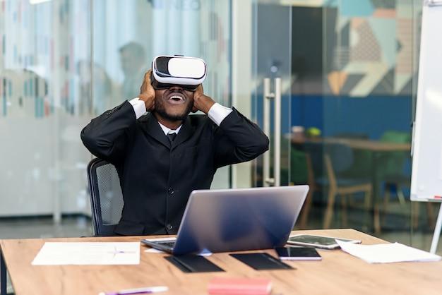 Портрет молодого афро-американского профессионала используя дополненную виртуальную реальность в современном офисе лофта. технология vr