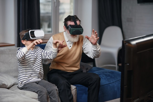 Портрет взволнованного старшего человека, использующего очки vr, сидящего на диване дома со смеющимся внуком около него