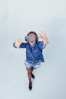 Брюнетка красивая женщина позирует в студии, носить джинсовую одежду, используя vr-очки виртуальной реальности гарнитуры