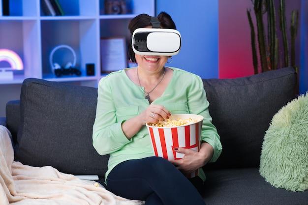 Старший женщина носить гарнитуру vr и сенсорный виртуальный экран ночью. счастливый зрелая женщина носить гарнитуру виртуальной реальности у себя дома.