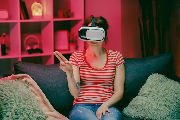 女性はvrヘッドセットを着用し、夜に仮想画面をタッチ