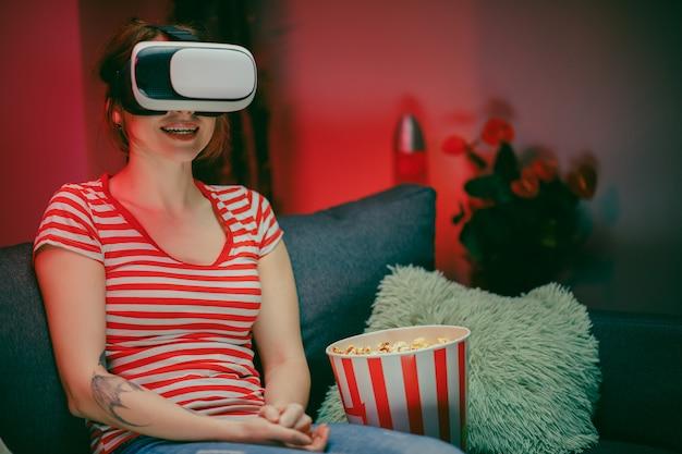 ソファに座ってvrヘッドセットを持ち、ポップコーンを食べて笑顔で何かを見ている若い女性の肖像画