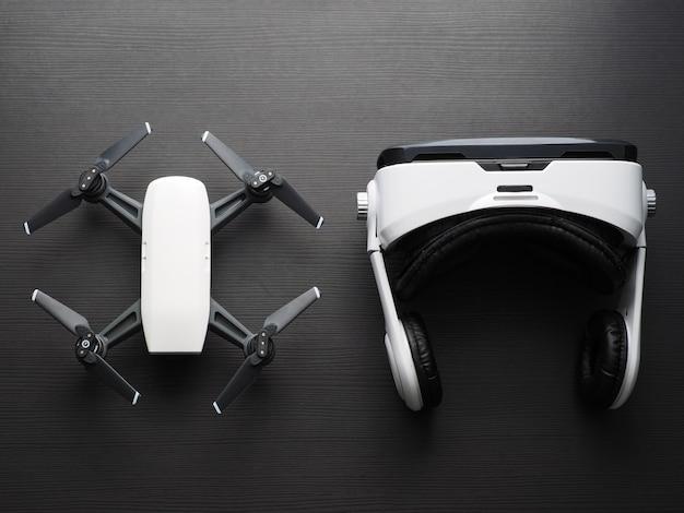 仮想現実の眼鏡とドローン。暗い木製のテーブルのクアッドコプターとvrヘッドセットの平面図。