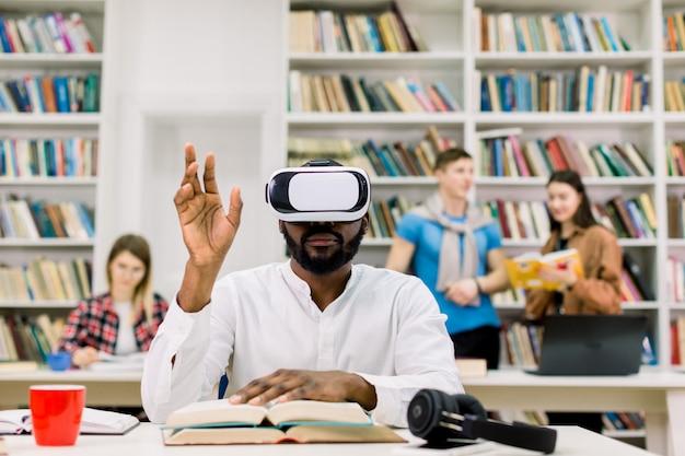 Портрет мужчины африканского университета студент чтения в библиотеке, носить симуляторы vr и трогательные страницы виртуальной книги в воздухе