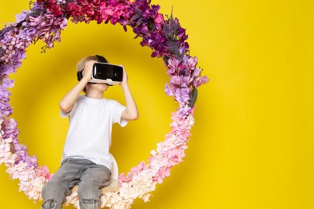 Вид спереди блондин мальчик vr вокруг цветка сделал стенд в белой футболке на желтом полу