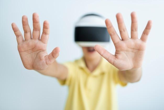 Ребенок вид спереди с очками vr и сфокусированными руками