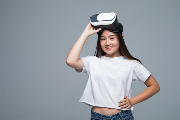 Молодая азиатская девушка смотря vr хотя и касание руки на воздухе на серой предпосылке