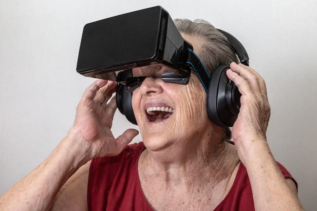 幸せな祖母は白い背景の上に現代のvrゴーグルガラスを使用します。新しいトレンドと技術コンセプトと面白い現役高齢者。