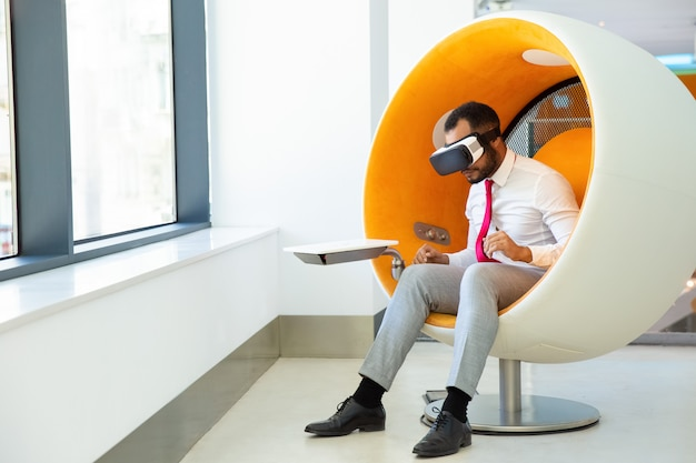Сосредоточенный афроамериканский пользователь, носящий очки vr