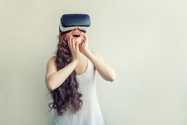 白で隔離バーチャルリアリティvrメガネヘッドセットを着て笑顔の若い女性