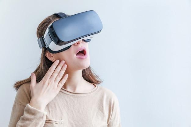 仮想現実vrメガネヘルメットヘッドセットを使用して身に着けている若い女性を笑顔します。