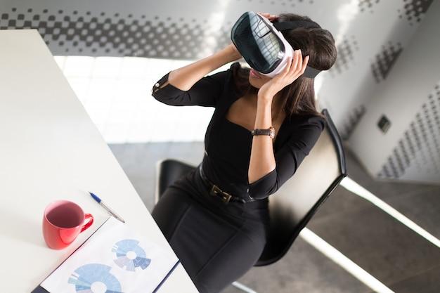 黒の強いスイートの女性はvrメガネのオフィスのテーブルに座る
