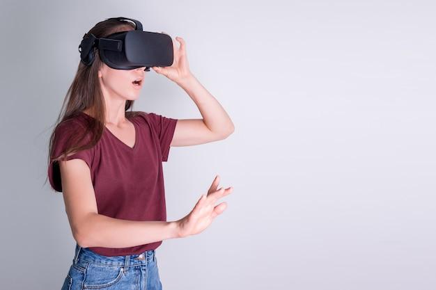 Изумленная позитивная женщина нося шлемофон изумлённых взглядов виртуальной реальности, коробку vr. связь, технология, новое поколение, концепция прогресса. девушка удивлена чему-то в виртуальной реальности. студия снятая на сером