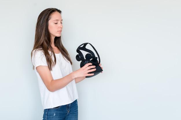 仮想現実を保持している若い女性は、ヘッドセット、vrボックスをゴーグルします。接続、技術、新世代、進歩のコンセプト。スタジオは灰色で撮影。