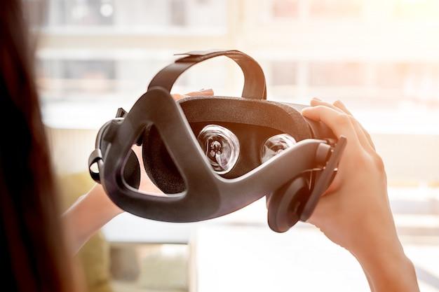 仮想現実ヘルメットを保持している手。将来の仮想ビジュアルのコンセプト、ゲームまたはvrテクノロジーのビデオ