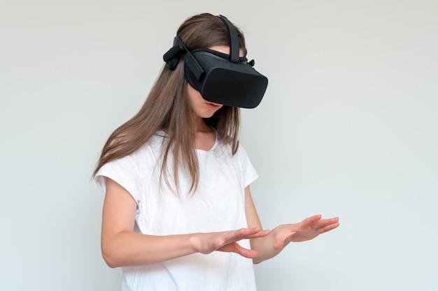 Усмехаясь шлемофон изумлённых взглядов виртуальной реальности положительной женщины нося, коробка vr. связь, технология, новое поколение, концепция прогресса. девушка пытается коснуться объектов в виртуальной реальности. студия снятая на сером