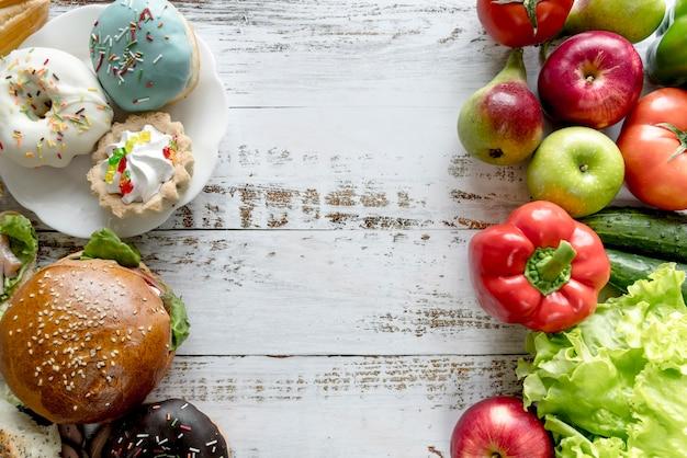 木製のテーブルで健康vs不健康な食べ物