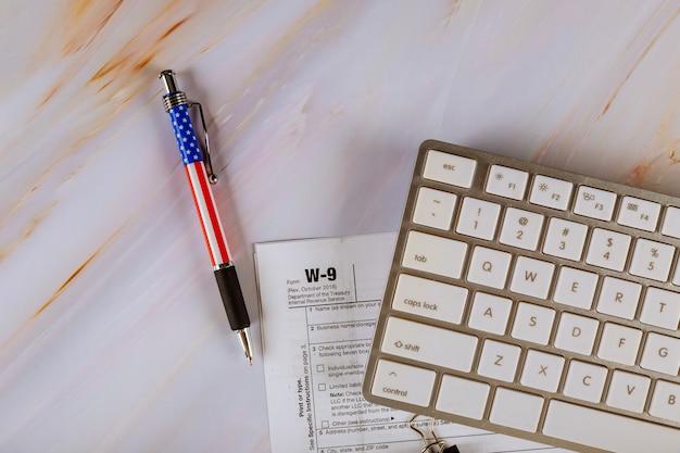 ペン、コンピューターキーボードを備えた内国歳入庁からのw-9米国連邦ビジネスファイナンス税フォーム