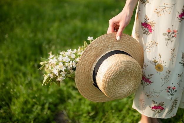 明るい夏のサンドレスを着た少女は、咲く自然を楽しみながら春の緑豊かな公園を散歩し、wの帽子と花を手に持っています。