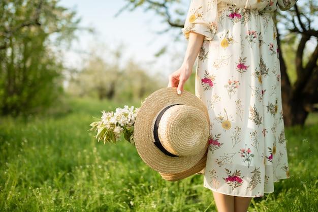 明るい夏のサンドレスの女の子は、咲く自然を楽しんでいる春の緑豊かな公園を散歩し、wの帽子と花を手に持っています