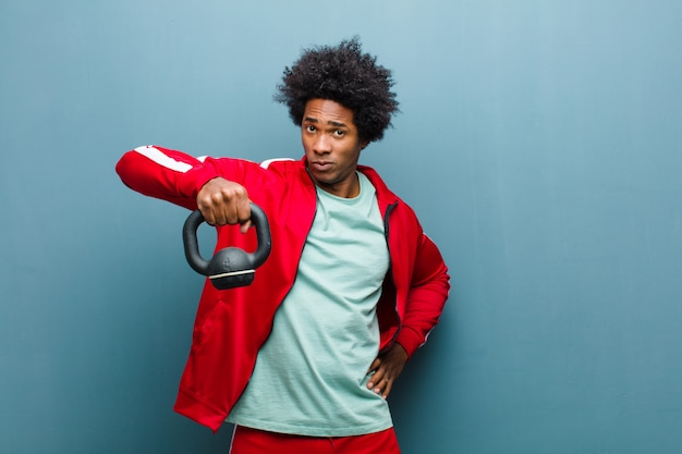 若い黒人男性スポーツダンベルブルーグランジwを持つ男
