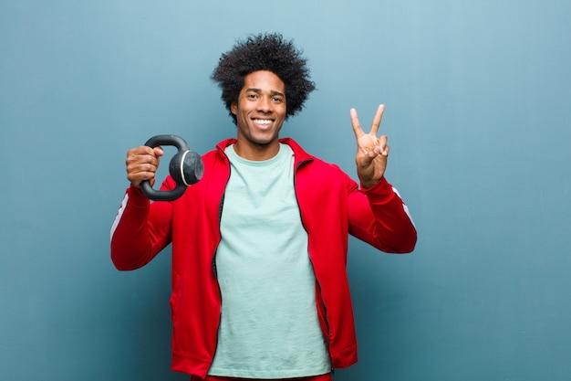 若い黒人男性スポーツ青いグランジwに対してダンベルを持つ男