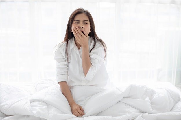 Азиатская женщина улыбается женщина, сидя на кровати и растяжения утром в спальне после w