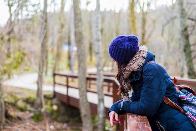 古い歩道橋近くに立っているバックパックで美しい少女のw肖像画