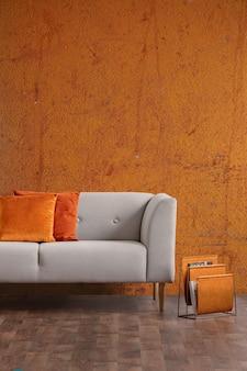 Интерьер гостиной ваби саби со старой оранжевой стеной и новым стильным диваном с подушками, реальное фото с копией пространства
