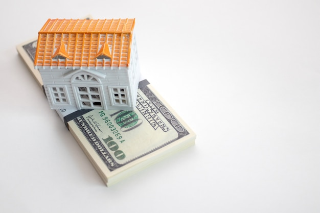 Wad of dollars and a house model on white background.