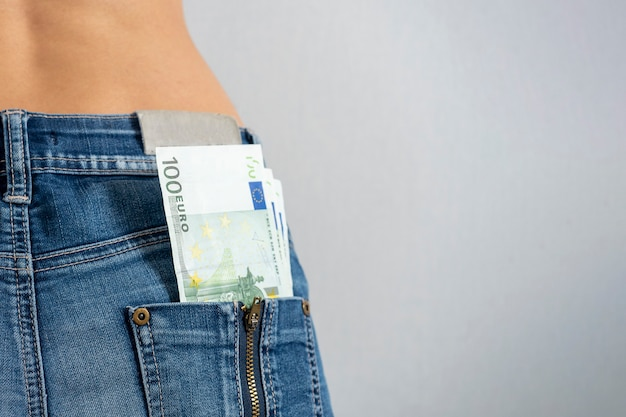 A wad of hundred-euro bills protrudes from the back pocket of women's jeans. horizontal photo, copy space. money in your pocket
