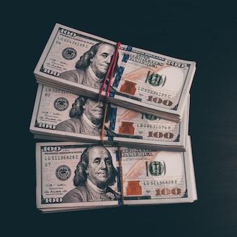 暗いテーブルに現金でドルの札束。 300ドルのパック。