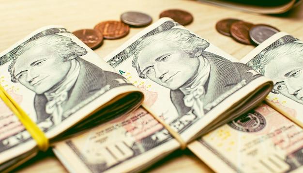 근접 촬영 사진에서 나무 테이블에 접힌 미국 달러 지폐의 뭉치