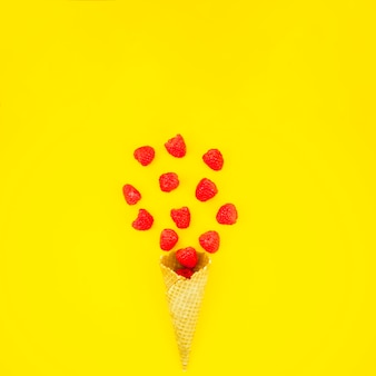 Wafer horn with raspberries on bright surface
