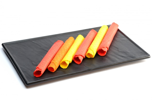 Wafer rolls of different colors on black stone board, on white