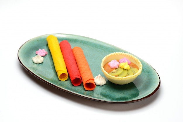 Wafer rolls with fruit sauce in a green plate