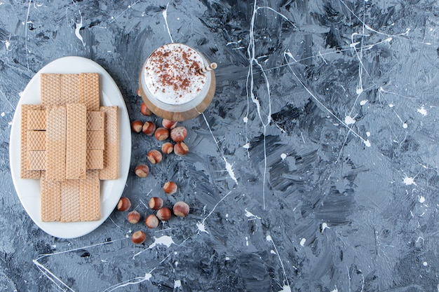 Bastoncini di wafer con noci di macadamia e una tazza di vetro di gustoso caffè caldo.