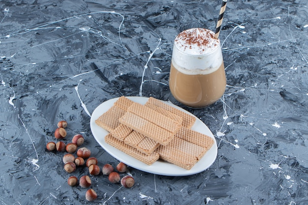 Wafer sticks with macadamia nuts and a glass cup of tasty hot coffee .